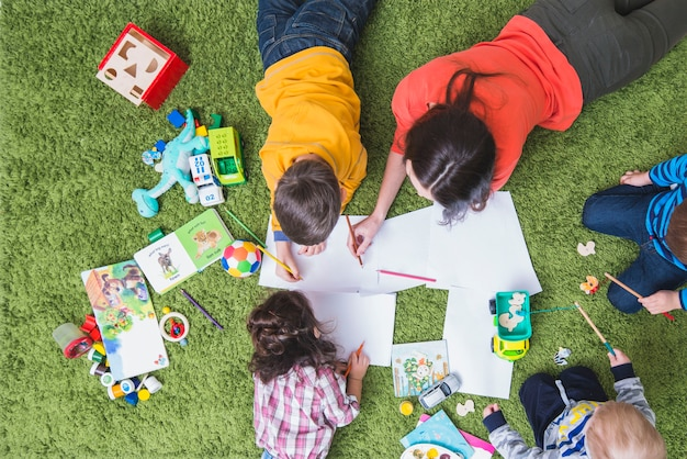 Kinder zeichnen und spielen auf teppich