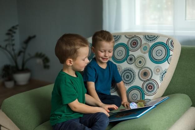 Kinder zu hause schauen sich ein buch auf dem sofa an. hohe qualität