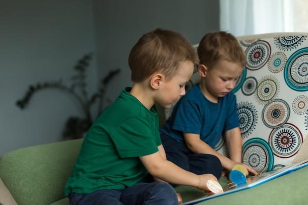Kinder zu hause schauen sich ein buch auf dem sofa an.