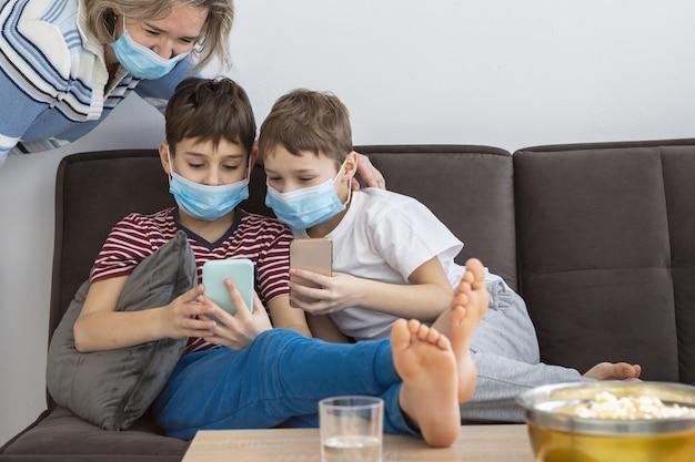 Kinder zu hause tragen medizinische masken und spielen auf smartphones