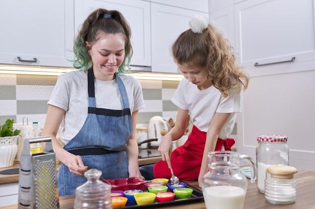 Kinder, zwei mädchen, schwestern, die muffins in der heimischen küche zubereiten. alte teenager-mädchen mit jüngeren zusammen in der küche. freundliche familie, spaß haben, hausgemachtes backen, häusliches leben
