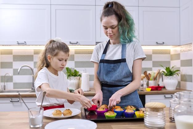 Kinder zwei mädchenschwestern, die muffins in der heimischen küche zubereiten. alte teenager-mädchen mit jüngeren zusammen in der küche. freundliche familie, spaß, hausgemachtes backen, häusliches leben