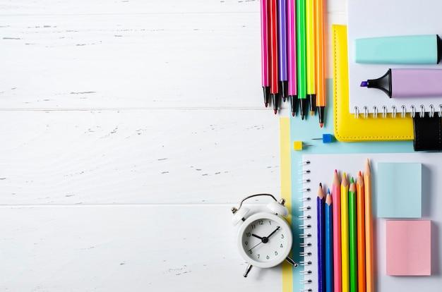 Kinderaccessoires für studium, kreativität und büromaterial auf weißem holzhintergrund. zurück zum schulkonzept. speicherplatz kopieren.