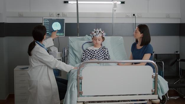 Kinderärztin bespricht tomographie-expertise während der überwachung der krankheitsentwicklung während der genesungsberatung. krankes kind mit eeg-gehirnsensor-headset in der krankenstation
