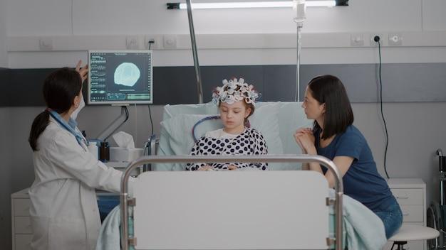 Kinderärztin, die den krankheitsverlauf überwacht und gleichzeitig die expertise der hirntomographie analysiert