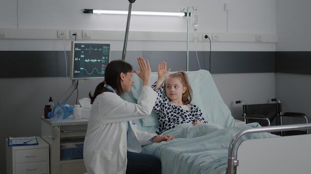 Kinderärztin, die sich entspannt, während sie mit einem kranken mädchenpatienten high five spielt