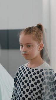 Kinderärztin, die während der genesungsuntersuchung in der krankenstation die lungen des patienten mit einem medizinischen stethoskop hört. krankes mädchen im krankenhaus, das sich nach einer medikamentösen operation erholt