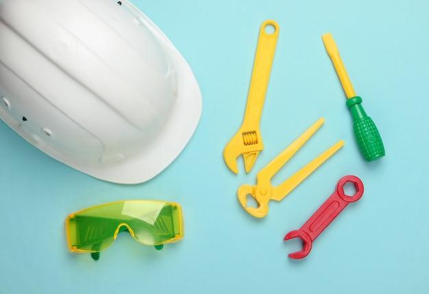 Kinderarbeitsgeräte und helm auf blau .. ingenieur, baumeister. kindheitskonzept