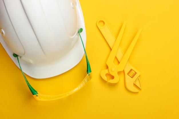 Kinderarbeitsgeräte und helm auf gelb .. ingenieur, baumeister. kindheitskonzept