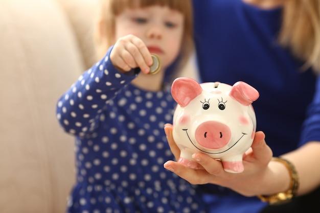 Kinderarm des kleinen mädchens, der münzen in das sparschwein steckt