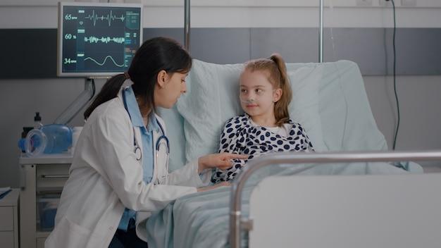 Kinderarzt, beraterin, ärztin, die mit kleinem kind interagiert, das high five gibt