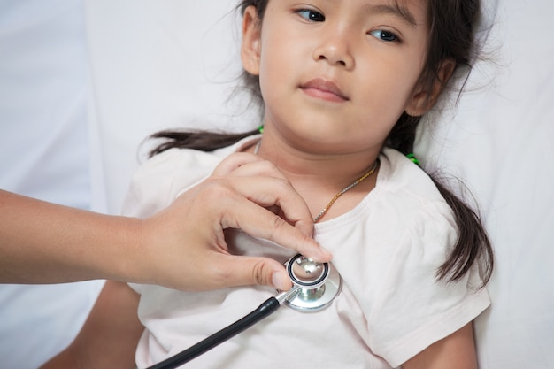 Kinderarzt, der das asiatische herz des kleinen mädchens überprüft