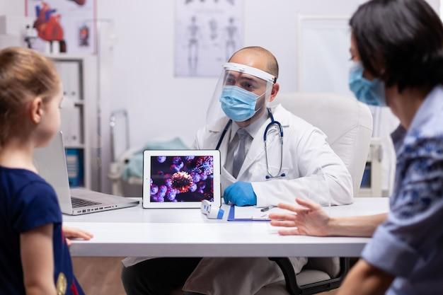 Kinderarzt, der das covid19-virus auf dem tablet-pc zeigt und über professionelle behandlung diskutiert