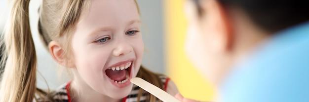 Kinderarzt, der den hals eines kleinen mädchens mit spachtel untersucht