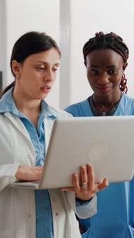 Kinderarzt, der über die genesung von kinderkrankheiten spricht und medizinisches fachwissen auf dem laptop für die afroamerikanische krankenschwester zeigt, während er in der krankenstation arbeitet. mädchen, das im bett liegt und auf die diagnose mit den eltern wartet