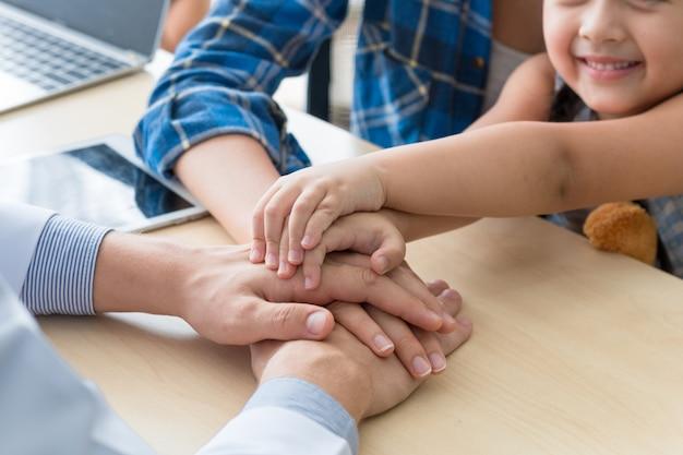 Kinderarzt (doktor) mann schließen sich die hände zusammen, beruhigend und besprechen kind an der chirurgie.