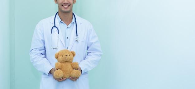 Kinderarzt hält teddybär.
