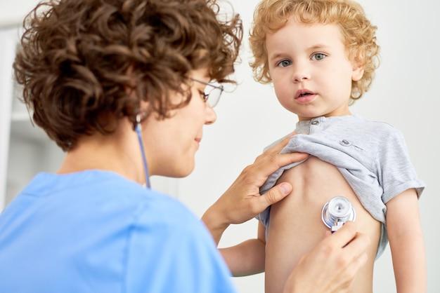 Kinderarzt hört auf die atmung des kindes