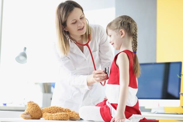 Kinderarzt hört mit dem stethoskop des kleinen mädchens auf atmung und herzschlag