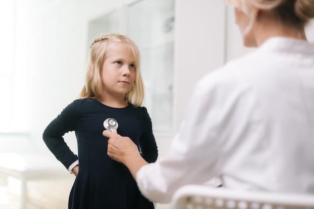 Kinderarzt mit stethoskop untersucht junges mädchen mit blonden haaren