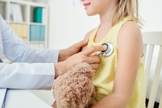 Kinderarzt prüft herzschlag des mädchens