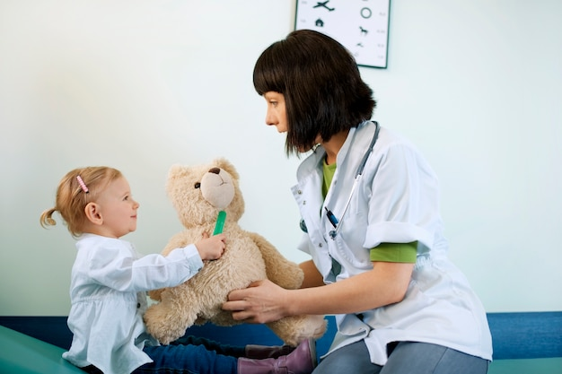 Kinderarzt spielt mit kind in der arztpraxis