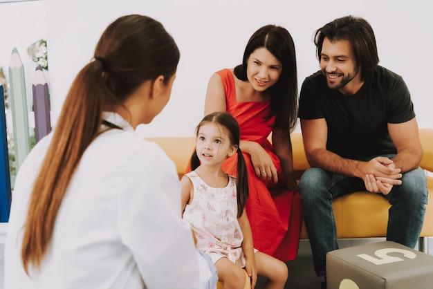Kinderarzt spricht mit kleinem mädchen im büro