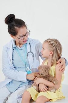 Kinderarzt umarmt kleines mädchen