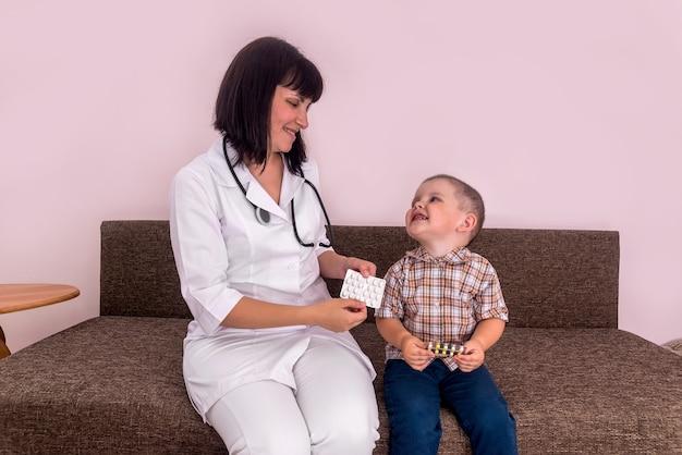 Kinderarzt und kleiner junge mit pillen im blister