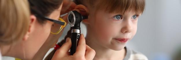 Kinderarzt untersucht das ohr eines kranken kindes