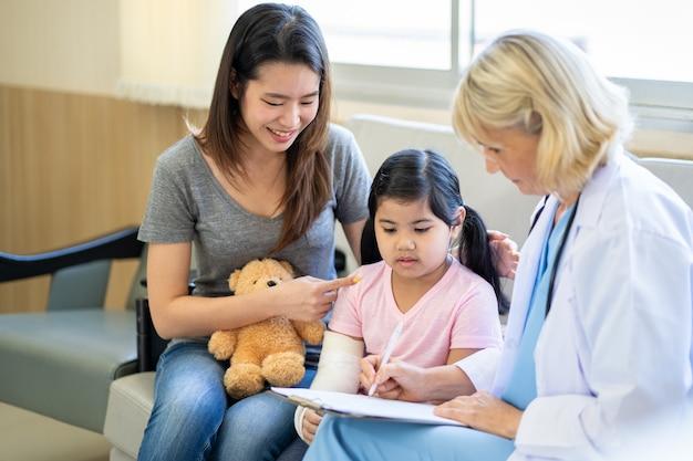 Kinderarzt untersucht kleines asiatisches mädchen mit gebrochenem arm und gips im krankenhaus