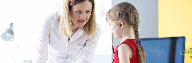 Kinderarzt zusammen mit kleinen mädchen spielen medizin mit spielzeug. kindheitsangst vor ärzten konzept