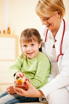Kinderarztdoktor, der dem kleinen patienten süßigkeit gibt