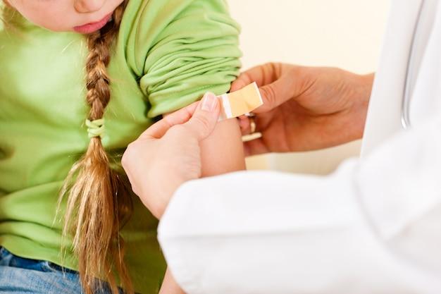 Kinderarztdoktor, der spritze am kind anwendet