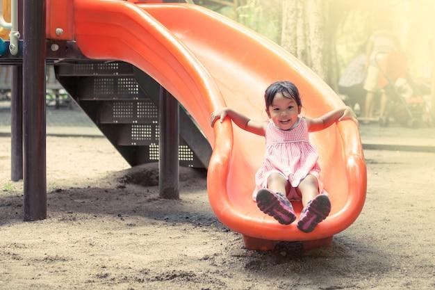 Kinderasiatisches mädchen, das spaß hat, schieber im spielplatz zu spielen