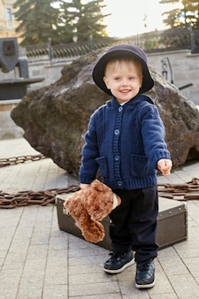 Kinderbaby in retro-herbstfrühlingskleidung. kleines kind sitzt lächelnd in der natur, schal um den hals, kühles wetter. helle emotionen auf seinem gesicht. russland, swerdlowsk, 29. september 2018