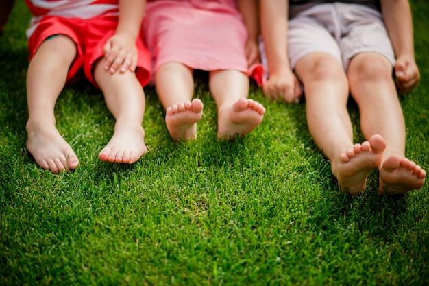 Kinderbeine auf dem rasen. nackte beine von kleinen mädchen sitzen auf der wiese. geringe tiefenschärfe, kinder sitzen auf dem rasen mit bloßen beinen