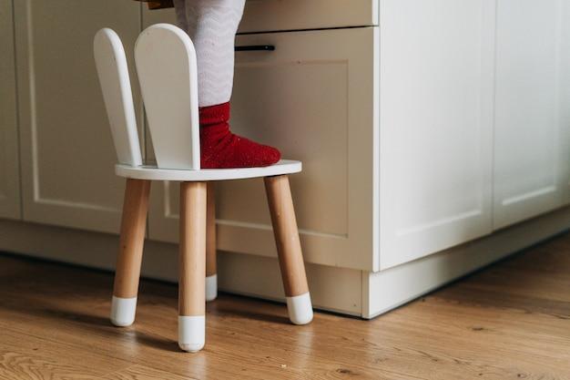 Kinderbeine auf scandi-artkinderstuhl an der küche. erwachsen . hochwertiges foto