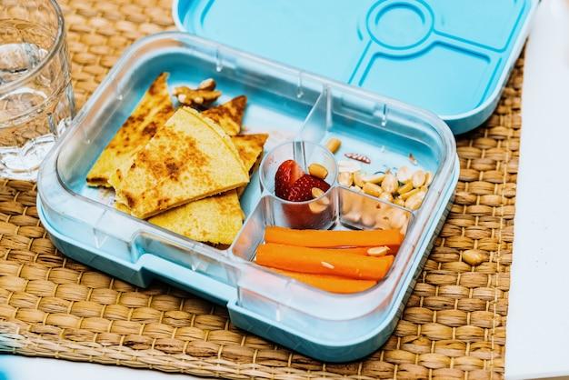 Kinderbrotdose mit gesunden karotten, erdbeeren und omelett.
