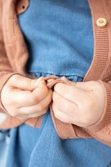 Kinderentwicklung nahaufnahme von kinderhänden, die lernen, sich anzuziehen, praktische montessori-fähigkeiten zuzuknöpfen