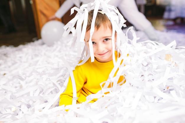 Kinderfest. little boy, das mit papierkonfettis spielt.