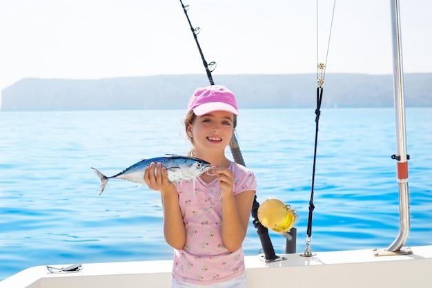 Kinderfischen des kleinen mädchens im boot, das wenig thunfischfang hält