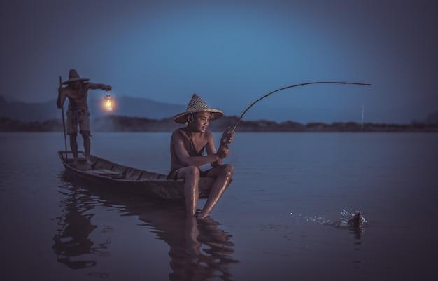 Kinderfischer mit anziehenden fischen des vaters auf seefluß thailand