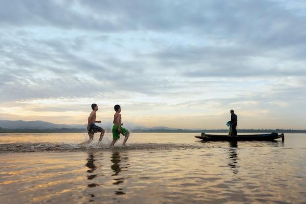 Kinderfischer werfen immer noch fischerdörfer. glücklich das lächeln der kinder. die fischer werfen auf dem alten hölzernen boot einen schönen morgensonnenaufgang.