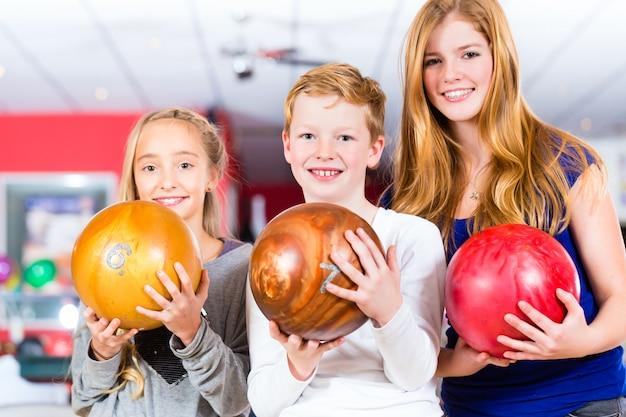 Kinderfreunde, die zusammen in der bowlingspielmitte spielen