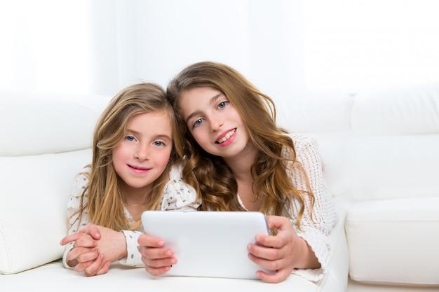 Kinderfreunde scherzen die mädchen, die zusammen mit tabletten-pc spielen