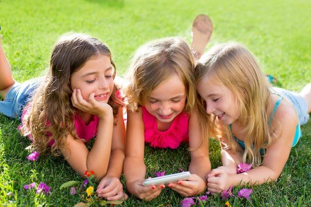 Kinderfreundinnen, die internet mit smartphone spielen