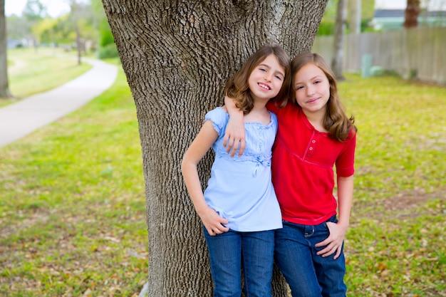 Kinderfreundmädchen, die das ohr spielen in einem parkbaum flüstern