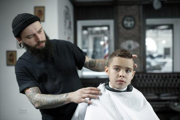 Kinderfriseur, der kleinen jungen gegen einen dunklen hintergrund schneidet. zufriedener süßer vorschulkind, der den haarschnitt bekommt. die hand des meisters hat tätowierung mit dem wort rasur