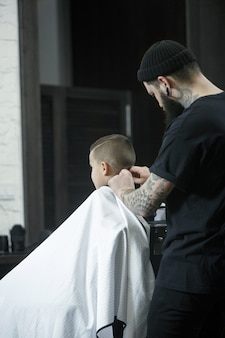 Kinderfriseur, der kleinen jungen gegen einen dunklen hintergrund schneidet. zufriedener süßer vorschulkind, der den haarschnitt bekommt.